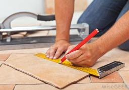 person-with-ruler-installing-tile-floor
